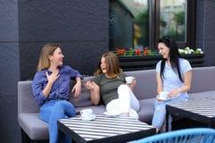 Amis féminins riant, parlant au café et au café potable Photos stock