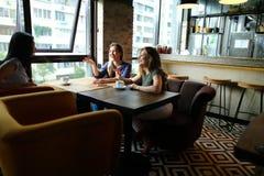 Amis féminins riants s'asseyant au restaurant et parlant avec des tasses de café Photos stock