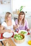 Amis féminins rougeoyants mangeant de la salade dans la cuisine Images stock