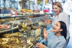 Amis féminins sélectionnant les chocolats et la confiserie fins au Ca Photo libre de droits