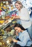 Amis féminins sélectionnant les chocolats et la confiserie fins au Ca Image libre de droits