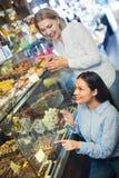 Amis féminins sélectionnant les chocolats et la confiserie fins au Ca Photographie stock libre de droits