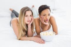 Amis féminins sérieux avec le bol de maïs éclaté se situant dans le lit Image stock