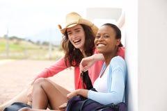 Amis féminins s'asseyant à la gare ferroviaire Photos stock