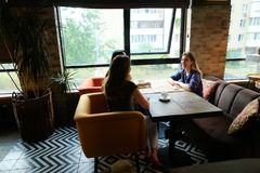 Amis féminins s'asseyant au café de restaurant, de parler et de boissons Photo stock