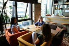 Amis féminins s'asseyant au café de café, de sourire et de boissons confortable Photo stock