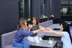 Amis féminins s'asseyant au café et tenant des mains Photo stock