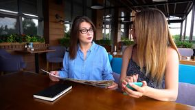 Amis féminins s'asseyant au restaurant et regardant le menu et le sma Photographie stock