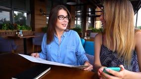 Amis féminins s'asseyant au restaurant et regardant le menu et le sma Image libre de droits