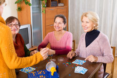 Amis féminins s'asseyant avec le loto Image libre de droits