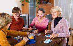 Amis féminins s'asseyant avec le loto Photos stock