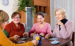 Amis féminins s'asseyant avec le loto Photographie stock libre de droits