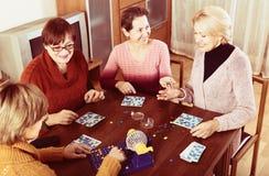 Amis féminins s'asseyant avec le loto Photographie stock