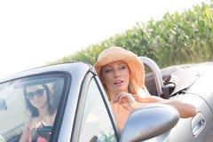 Amis féminins s'asseyant dans le convertible le jour ensoleillé Image stock