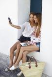 Amis féminins s'asseyant en porte prenant un selfie, Ibiza Photographie stock