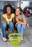 Amis féminins s'asseyant ensemble contre le lavage Photographie stock