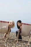 Amis féminins s'asseyant sur des chaises longues à la plage Images libres de droits