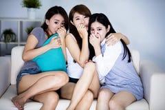 Amis féminins s'asseyant sur le film d'horreur de observation de sofa Image libre de droits