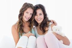 Amis féminins s'asseyant sur le lit avec le bras autour Image stock