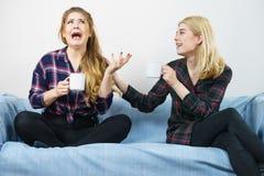Amis féminins s'asseyant sur le sofa ayant l'amusement Photographie stock