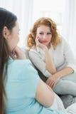 Amis féminins s'asseyant sur le sofa dans le salon Image libre de droits
