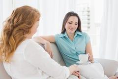 Amis féminins s'asseyant sur le sofa dans le salon Images stock