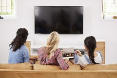 Amis féminins s'asseyant sur Sofa Watching Television Eating Candy Images libres de droits
