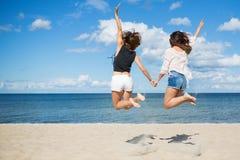 Amis féminins sautant sur la plage tenant des mains Photographie stock