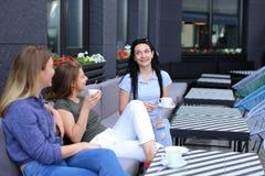 Amis féminins se reposant au café et au bavardage, café potable Photos stock