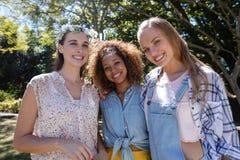 Amis féminins se tenant ensemble en parc Image stock