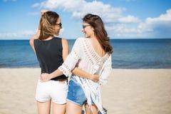 Amis féminins se tenant sur la plage s'embrassant Photographie stock