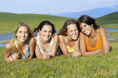 Amis féminins se trouvant ensemble sur l'herbe en parc Photo libre de droits