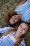 Amis féminins se trouvant ensemble sur l'herbe en parc Image libre de droits