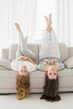 Amis féminins se trouvant sur le sofa avec des jambes dans le ciel dans le salon Photographie stock