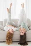 Amis féminins se trouvant sur le sofa avec des jambes dans le ciel dans le salon Photographie stock libre de droits