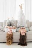 Amis féminins se trouvant sur le sofa dans le salon Photos stock