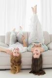 Amis féminins se trouvant sur le sofa dans le salon Photo stock