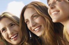 Amis féminins semblant partis tout en souriant Images stock