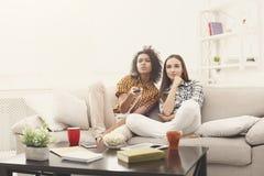 Amis féminins songeurs regardant la TV à la maison Images libres de droits