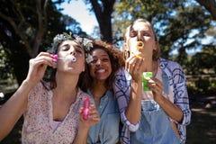 Amis féminins soufflant des bulles en parc Photographie stock libre de droits