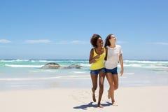 Amis féminins souriant et marchant sur la plage ensemble Image stock
