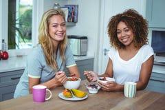 Amis féminins souriant tout en prenant le petit déjeuner dans la cuisine Photographie stock libre de droits