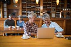 Amis féminins supérieurs à l'aide de l'ordinateur portable tandis que couples ayant le thé à l'arrière-plan Photo stock