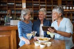 Amis féminins supérieurs à l'aide du comprimé numérique tout en ayant des boissons Photo libre de droits
