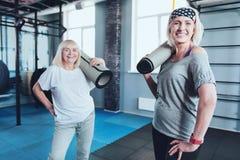 Amis féminins supérieurs adorables posant avec des tapis Photographie stock libre de droits