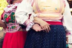 Amis féminins supérieurs anonymes dans des costumes de folklore Photographie stock libre de droits