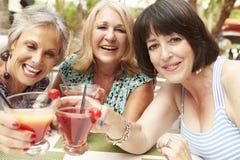 Amis féminins supérieurs appréciant des cocktails dans la barre ensemble Images libres de droits