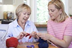Amis féminins supérieurs et mûrs tricotant à la maison ensemble Photo stock