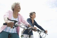 Amis féminins supérieurs montant des bicyclettes Images stock