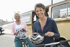 Amis féminins supérieurs tenant les casques de recyclage Photos stock